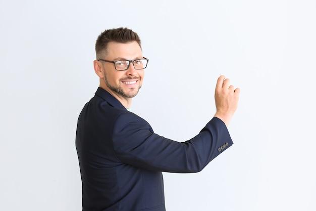Knappe mannelijke leraar die iets op wit schrijft