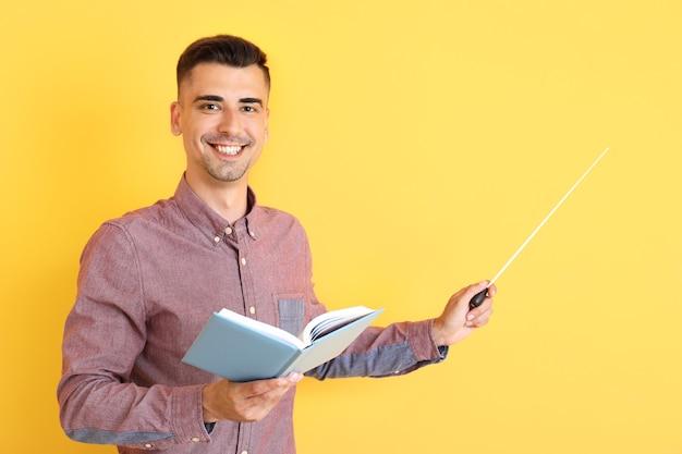 Knappe mannelijke leraar met boek en aanwijzer op kleur achtergrond