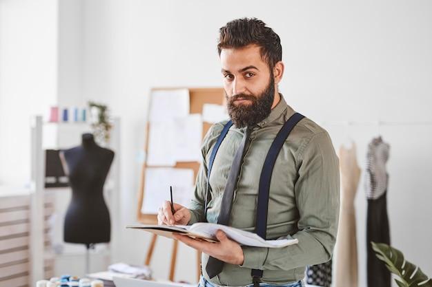 Knappe mannelijke modeontwerper in atelier met papieren