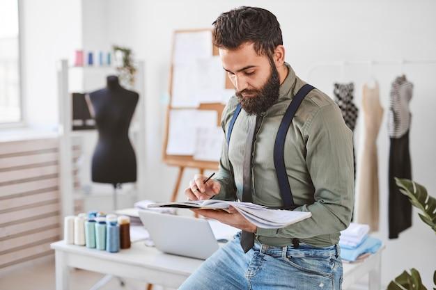 Knappe mannelijke modeontwerper in atelier