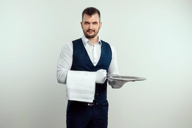 Knappe mannelijke ober, in wit overhemd, met een zilveren dienblad. het concept van bedienend personeel dat klanten bedient in een restaurant.