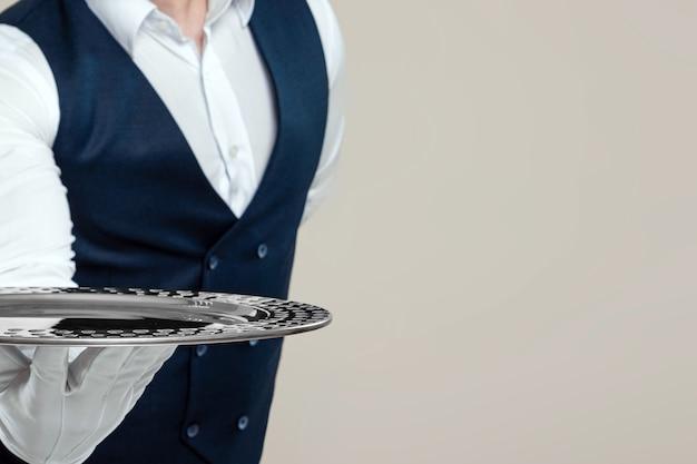 Knappe mannelijke ober, wit overhemd, houdt een zilveren dienblad vast, hand achter zijn rug. concept van bedienend personeel dat klanten in een restaurant bedient.