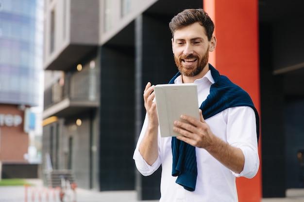 Knappe mannelijke ondernemer in wit overhemd praten en gebaren tijdens videogesprek op digitale tablet. bebaarde man die op straat staat en online conferentie heeft.