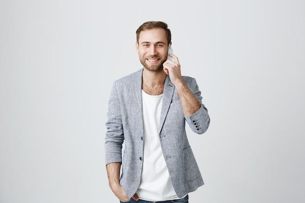 Knappe mannelijke ondernemer praten over de telefoon