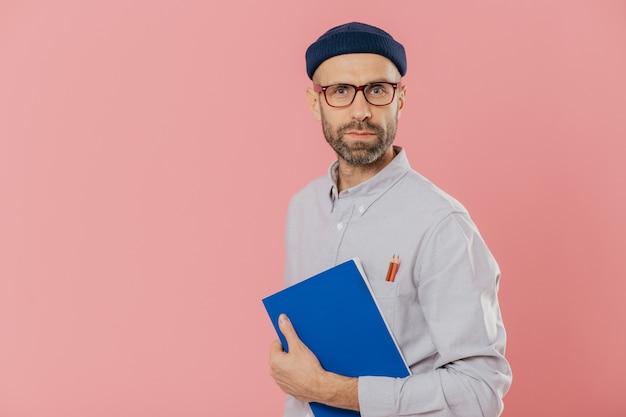 Knappe mannelijke ontwerper draagt stijlvolle kleding, heeft twee potloden in de zak van het shirt