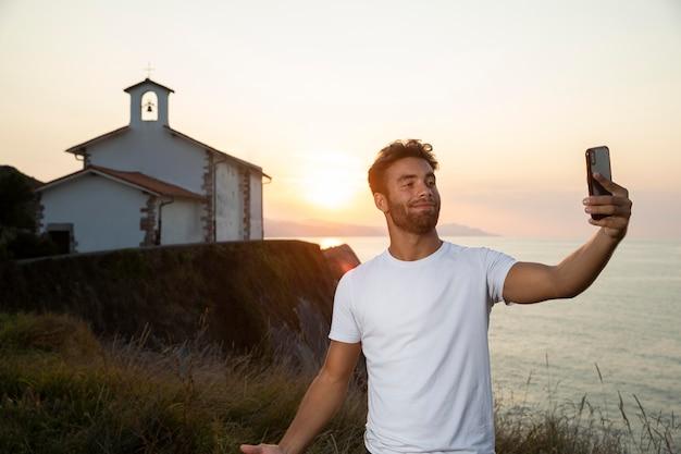 Knappe mannelijke reiziger die een selfie maakt