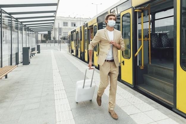 Knappe mannelijke reiziger gekleed in een stijlvol pak met witte koffer buitenshuis