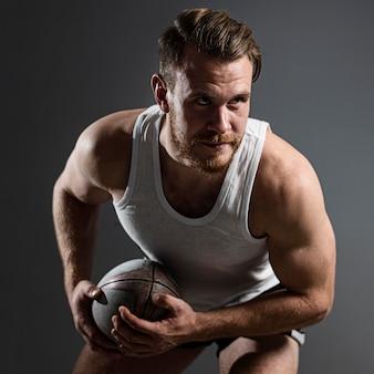 Knappe mannelijke rugbyspeler bal houden en poseren
