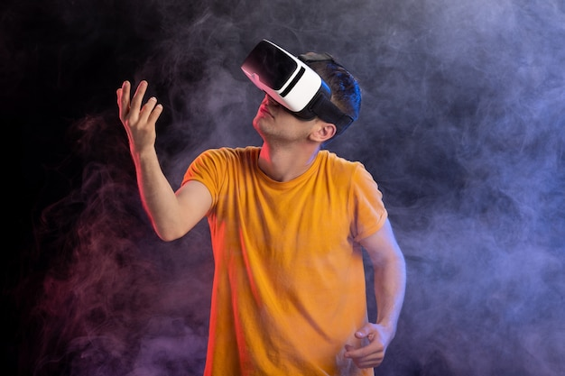Knappe mannelijke speelspel in virtual reality op donkere ondergrond