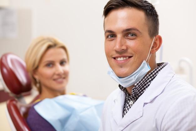 Knappe mannelijke tandarts die aan de camera, zijn gelukkige vrouwelijke patiënt op de achtergrond glimlachen.