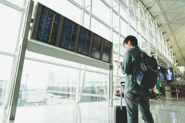 Knappe mannelijke toeristen gebruiken smartphones om vluchten te controleren voordat ze aan boord gaan.