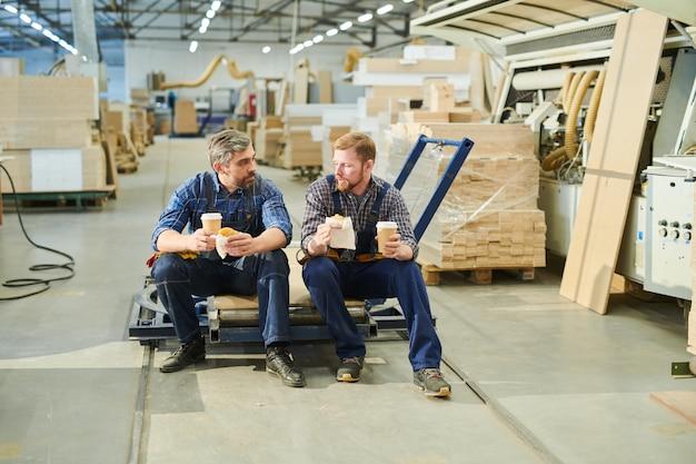 Knappe mannelijke werknemers in uniform chatten op pauze