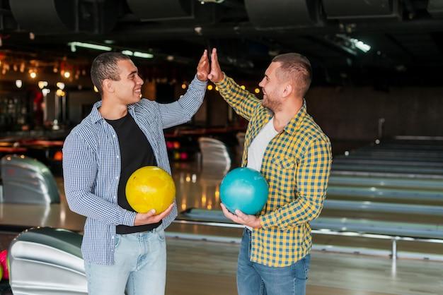 Knappe mannen die kleurrijke kegelenballen houden