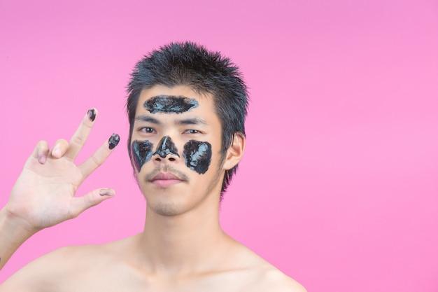 Knappe mannen die zwarte cosmetica op hun gezicht aanbrengen en een roze hebben.