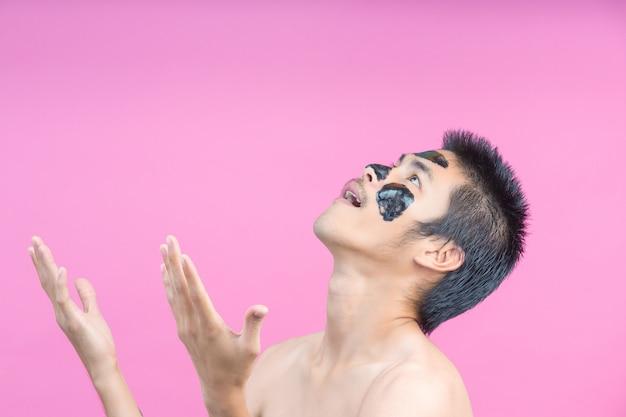 Knappe mannen die zwarte cosmetica op hun gezicht aanbrengen en verschillende houdingen met een roze tonen.