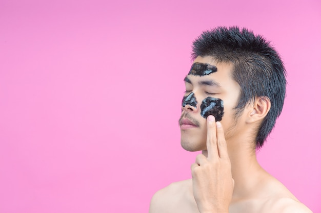Knappe mannen gebruiken hun handen om zwarte crème op hun gezicht aan te brengen en hebben een roze.