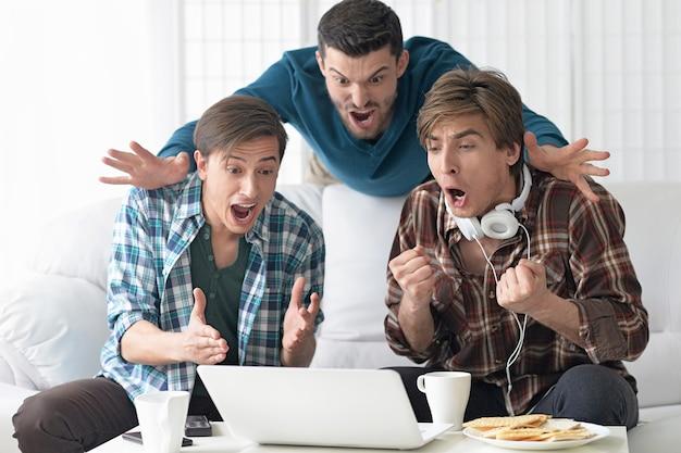 Knappe mannen kijken samen naar video op laptop