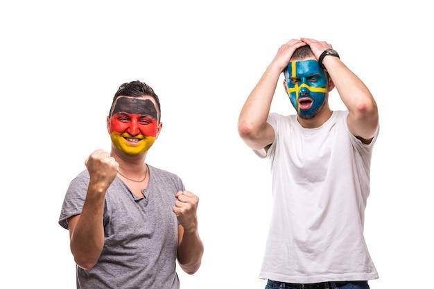 Knappe mannen supporters loyale fans van het zweedse nationale team en duitsland met geschilderde vlag. duitsland wint, zweden verliest. fans van emoties.