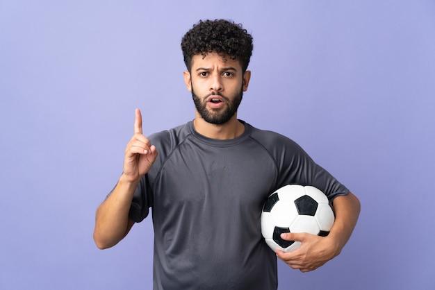 Knappe marokkaanse jonge voetballer man over geïsoleerd op paarse muur met de bedoeling de oplossing te realiseren terwijl hij een vinger opheft