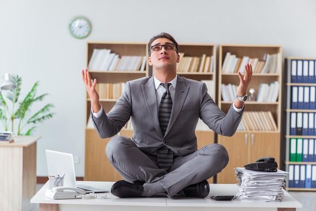 Knappe mediteren op het bureau