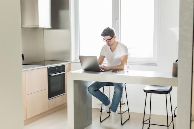 Knappe mens die aan laptop in de keuken thuis werkt