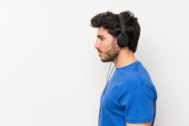 Knappe mens die aan muziek met hoofdtelefoons luistert