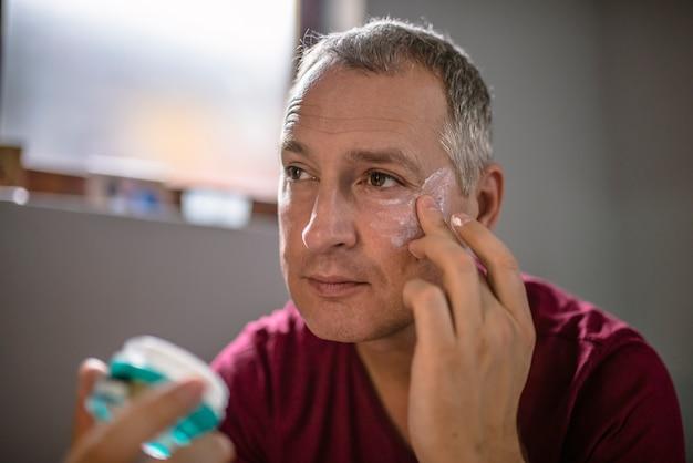 Knappe mens die anti-rimpelroom op zijn gezicht toepast. mens die vochtinbrengende crème toepast op zijn huid