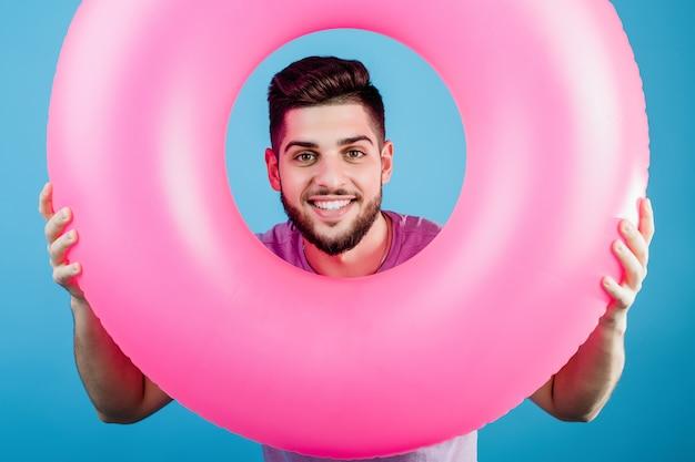 Knappe mens die door roze rubberring kijken voor zwemmen geïsoleerd over blauw