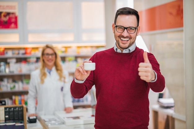 Knappe mens die duim-op en holding geneesmiddel in een drogisterij toont.