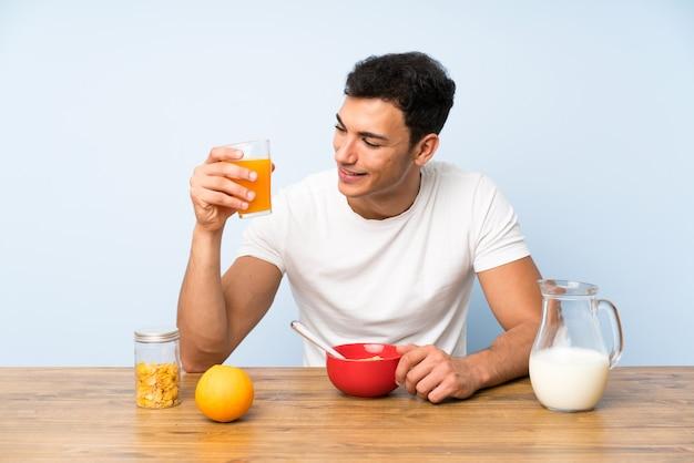 Knappe mens die een jus d'orange houdt