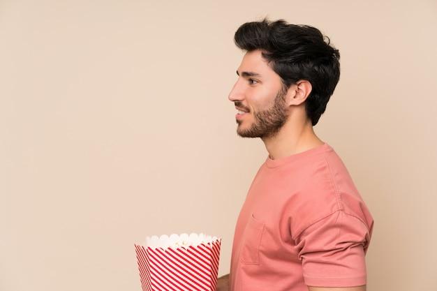 Knappe mens die een kom popcorns houdt