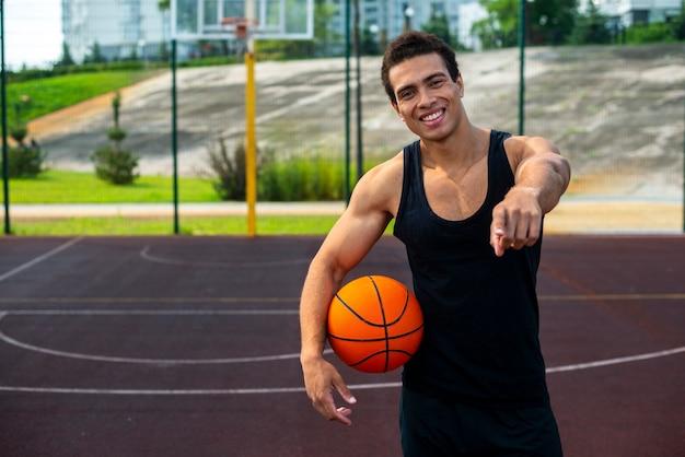 Knappe mens die een middelgroot schot van de basketbalbal houdt