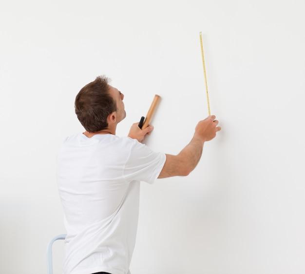 Knappe mens die een muur met heerser en hulpmiddelen bekijkt