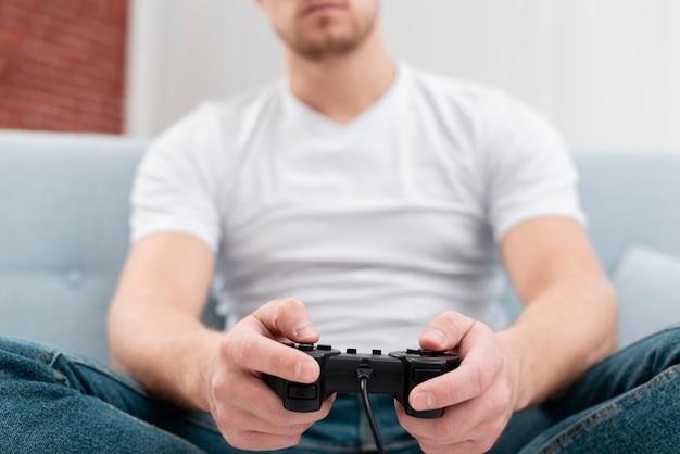 Knappe mens die een spel met een controlemechanismeclose-up speelt