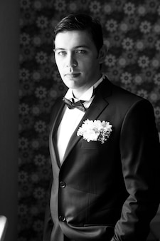 Knappe mens die en zich in huwelijkskostuum bevindt kijkt. zwart en wit