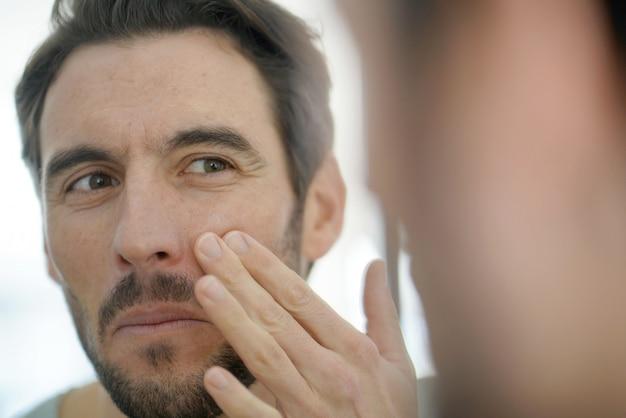 Knappe mens die gezichtsroom toepast die in spiegel kijkt
