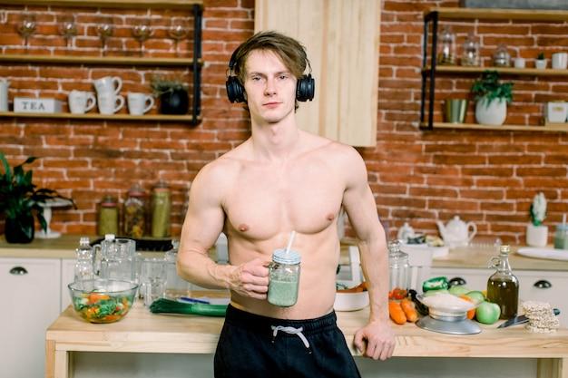 Knappe mens die groene smoothie in keuken drinken. jonge man luistert naar muziek in oortelefoons, drinkt smoothie tijdens het dansen. gezonde levensstijl en voeding