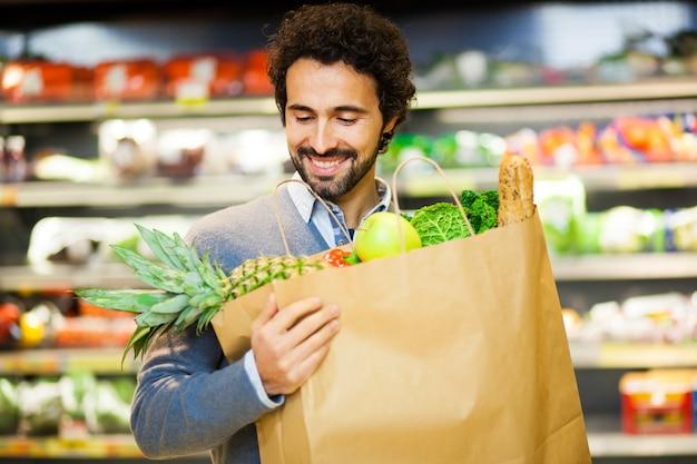 Knappe mens die in een supermarkt winkelt