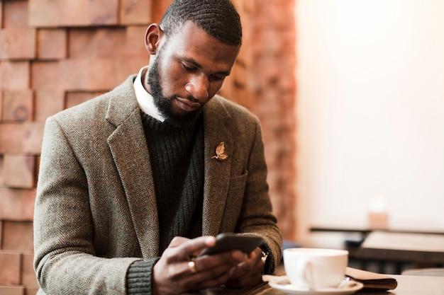 Knappe mens die in grijs jasje op zijn telefoon binnen kijkt