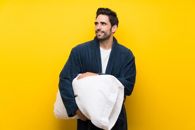 Knappe mens die in pyjama omhoog terwijl het glimlachen kijkt