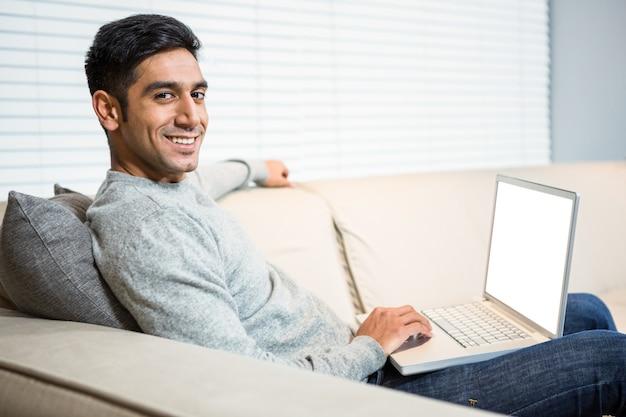 Knappe mens die laptop op bank met behulp van