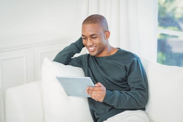 Knappe mens die laptop op de bank thuis met behulp van