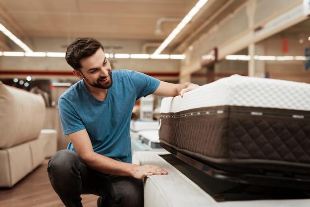 Knappe mens die matras in meubilairopslag kiezen