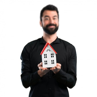 Knappe mens die met baard een klein huis op witte achtergrond houdt