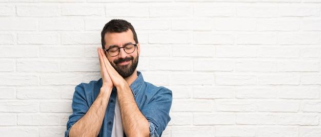 Knappe mens die met baard over witte bakstenen muur slaapgebaar in aanbiddelijke uitdrukking maken