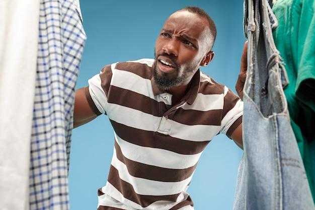Knappe mens die met baard overhemd in een winkel kiezen