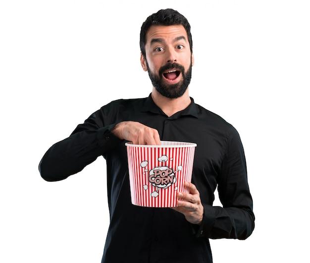 Knappe mens die met baard popcorns op witte achtergrond eet