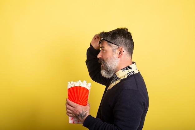 Knappe mens die met de zonnebril van het cameraprofiel een dooshoogtepunt van popcorn op gele achtergrond houden.