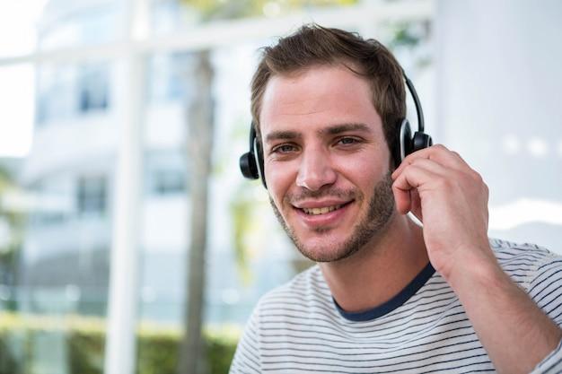 Knappe mens die met hoofdtelefoon in een helder bureau werkt