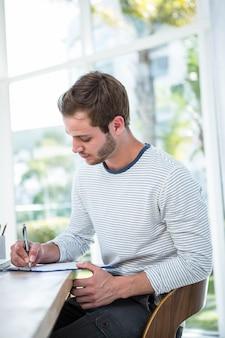 Knappe mens die nota's over klembord in een helder bureau neemt